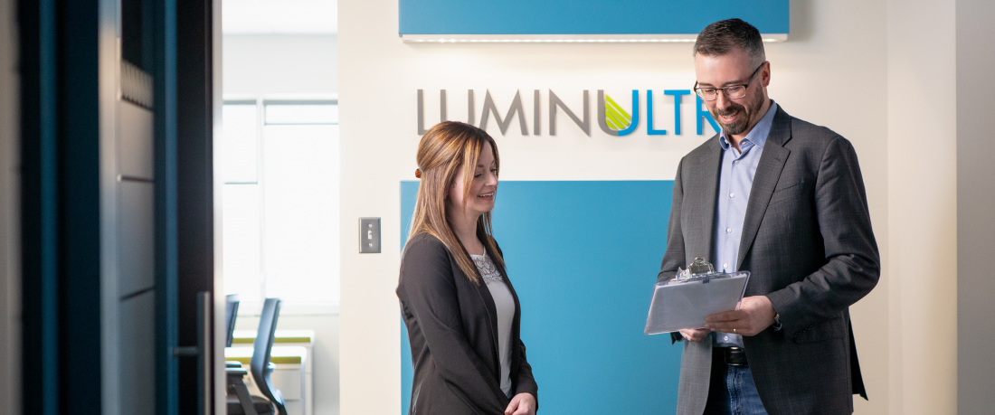 two employees chat in the LuminUltra lobby
