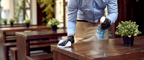 waiter disinfecting table